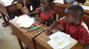 Dzieci z Kiabakari rysujące prace na wystawę w Brzeźnicy